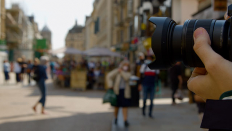 Close-Up-Shot-of-Man-Using-Focus-Ring-On-Camera-In-Busy-Street