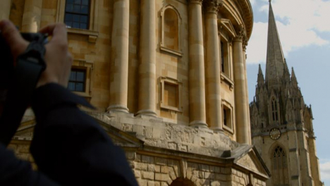 Tilting-Shot-of-Someone-Taking-a-Photo-of-Radcliffe-Camera-Building-In-Oxford