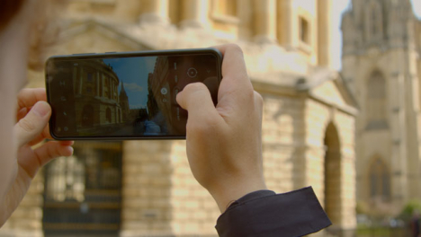 Over-the-Shoulder-Shot-of-Someone-Taking-Photos-On-Phone-of-Radcliffe-Camera-Building