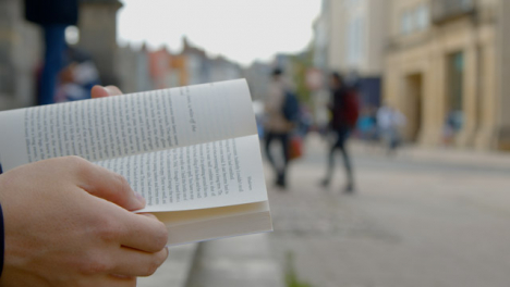 Close-Up-Shot-of-Someone-Reading-a-Book-On-Clarendon-Building-Steps-In-Oxford