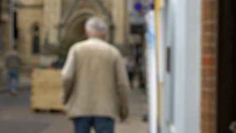 Defocused-Shot-of-Elderly-Man-Walking-Down-Quiet-Street-In-Oxford