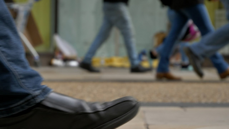 Defocused-Long-Shot-of-Feet-Walking-Past-Homeless-Persons-Belongings-In-Doorway-01