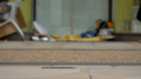 Defocused-Long-Shot-of-Feet-Walking-Past-Homeless-Persons-Belongings-In-Doorway-02