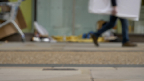 Defocused-Long-Shot-of-Feet-Walking-Past-Homeless-Persons-Belongings-In-Doorway-03