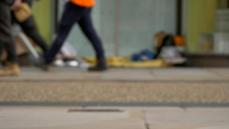 Defocused-Long-Shot-of-Feet-Walking-Past-Homeless-Persons-Belongings-In-Doorway-04