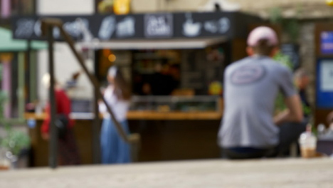 Defocused-Shot-of-Young-Girls-Walking-Away-from-Outdoor-Coffee-Stall-In-Oxford