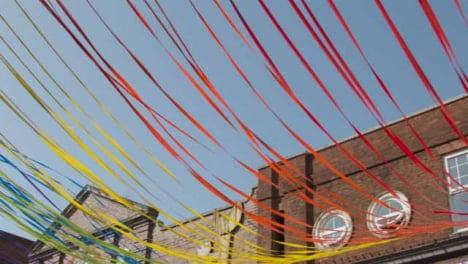 Low-Angle-Panning-Shot-of-Decorative-Ribbons-Tied-to-Building-