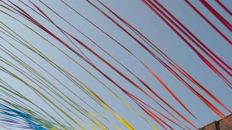 Low-Angle-Panning-Shot-of-Decorative-Ribbons-Tied-to-Buildings