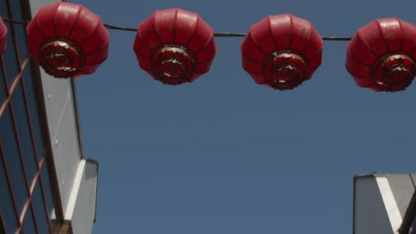 Low-Angle-Tracking-Shot-of-Chinese-Lanterns-Hanging-from-Buildings-