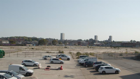 Tilting-Shot-of-Cars-Parked-In-Front-of-Desolate-Construction-Site