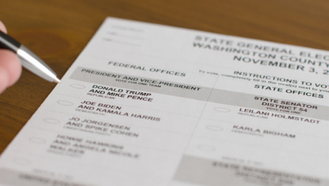 Close-Up-Hand-Deciding-to-Vote-for-Trump-or-Biden-on-Ballot-Paper