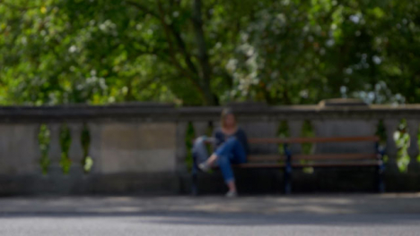Defocused-Shot-of-People-and-Traffic-Moving-In-Front-of-Woman-Sat-On-Bench-01
