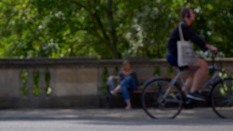 Defocused-Shot-of-People-and-Traffic-Moving-In-Front-of-Woman-Sat-On-Bench-02