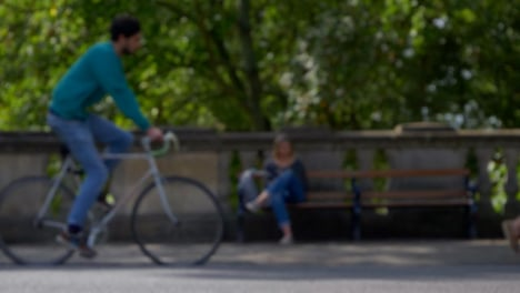 Defocused-Shot-of-People-and-Traffic-Moving-In-Front-of-Woman-Sat-On-Bench-03