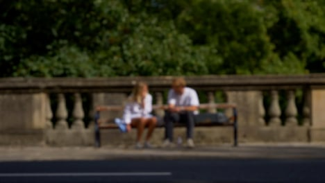 Defocused-Shot-of-People-and-Traffic-Moving-In-Front-of-Couple-Sat-On-Bench-01