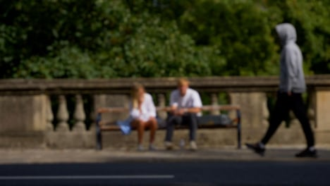 Defocused-Shot-of-People-and-Traffic-Moving-In-Front-of-Couple-Sat-On-Bench-02