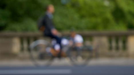 Defocused-Shot-of-Traffic-and-People-Moving-In-Front-of-Couple-Sat-On-Bench-02