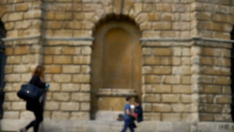 Defocused-Shot-of-Person-Eating-Lunch-In-Alcove-of-Oxfords-Radcliffe-Camera-Building-