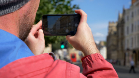 Over-the-Shoulder-Shot-of-Man-Taking-Photo-On-Phone-of-Old-Oxford-Buildings-03