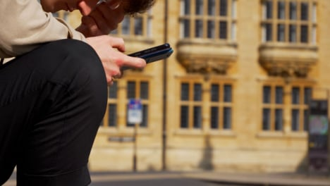 Close-Up-Shot-of-Man-Looking-at-Phone-On-Old-Street-In-Oxford-01
