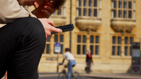 Close-Up-Shot-of-Man-Looking-at-Phone-On-Old-Street-In-Oxford-02