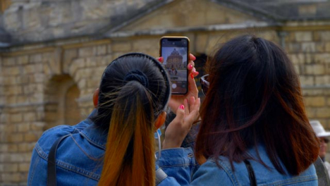 Over-the-Shoulder-Shot-of-Two-Friends-Taking-Photo-of-Radcliffe-Camera-Building