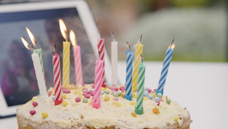 Candles-Being-Blown-Out-On-Birthday-Cake-As-Grandparents-Watch-Through-Video-Call