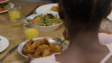 Young-Girl-Plating-Up-Some-Chicken-Onto-Plate-During-Dinner