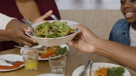 Woman-Passing-Bowl-of-Salad-to-Man-at-Family-Dinner-
