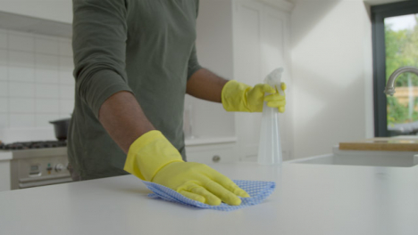 Man-Cleaning-Kitchen-Surface-with-Rubber-Gloves-and-Disinfectant-Spray