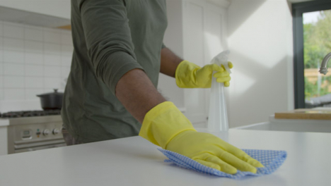 Man-Cleaning-Kitchen-Work-Surface-with-Rubber-Gloves-and-Disinfectant-Spray