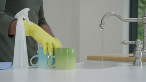 Man-Cleaning-a-Mug-Under-Running-Water-from-Kitchen-Tap-