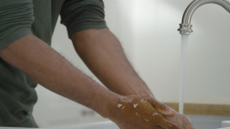 Man-Cleaning-Hands-with-Soapy-Water-Under-a-Running-Tap-