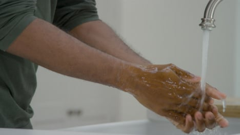 Man-Cleaning-His-Hands-with-Soapy-Water-Under-a-Running-Tap-