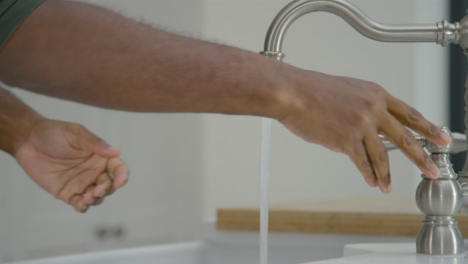 Man-Cleaning-His-Hands-with-Soapy-Water-Under-Running-Tap-