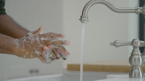 Man-Cleaning-His-Hands-with-Soap-Under-Running-Tap-Water