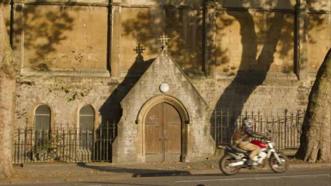 Wide-Shot-of-Motorcyclist-Riding-Past-Doors-to-St-Nicholas-Church-In-Bristol-
