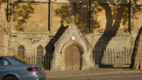 Wide-Shot-of-Car-and-Cyclist-Passing-Past-Doors-to-St-Nicholas-Church-In-Bristol-