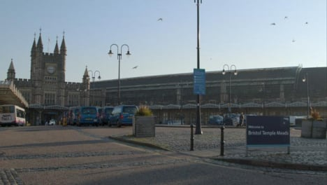 Wide-Shot-of-Birds-Flying-Around-Exterior-of-Bristol-Temple-Meads-Train-Station-