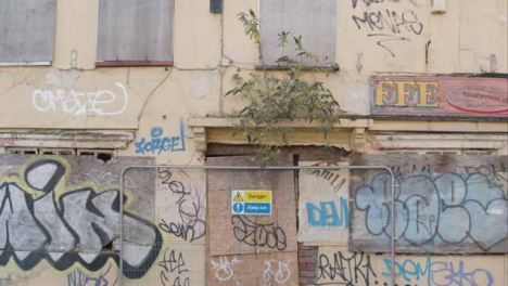 Tilting-Shot-of-Boarded-Up-and-Dilapidated-Building-In-Bristol-England