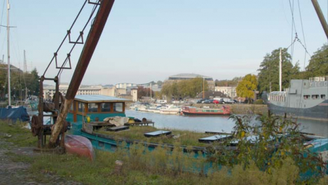 Rising-Shot-of-Rusted-Crane-Next-to-River-In-Bristol-England-