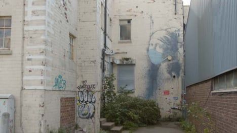 Wide-Shot-of-Banksy-Girl-Wearing-Pearl-Earrings-Artwork-In-Bristol-England