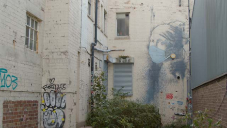 Tracking-Shot-Approaching-Banksy-Girl-Wearing-Pearl-Earrings-Artwork-In-Bristol-England