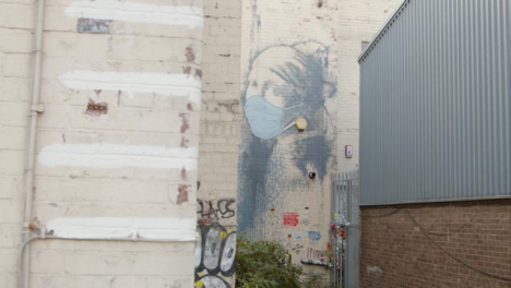 Sliding-Shot-Revealing-Banksy-Girl-Wearing-Pearl-Earrings-Artwork-In-Bristol-England