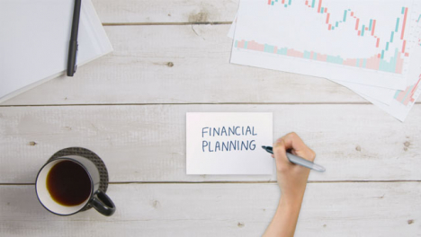 Top-Down-View-of-Woman-Writing-Financial-Planning-On-Paper-with-Business-Documents