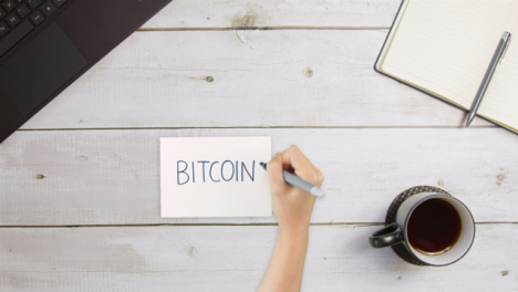 Top-Down-View-of-Woman-Writing-Bitcoin-On-Paper-with-Laptop-and-Notebook