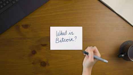 Top-Down-View-of-Woman-Writing-What-Is-Bitcoin-On-Paper-with-Notebook-and-Laptop