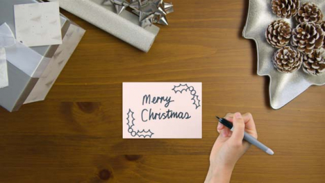Top-Down-View-of-Hand-Writing-Merry-Christmas-On-Paper-with-Christmas-Presents