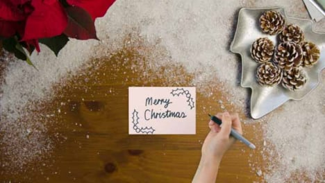 Top-Down-View-of-Hand-Writing-Merry-Christmas-On-Paper-with-Christmas-Decorations