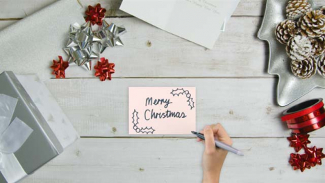Top-Down-View-of-Hand-Writing-Merry-Christmas-On-Paper-with-Christmas-Decorations-and-Gifts